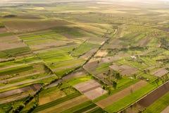 Vista aerea sopra una bella scena rurale con i campi e gli alberi verdi all'ora dorata in primavera fotografia stock