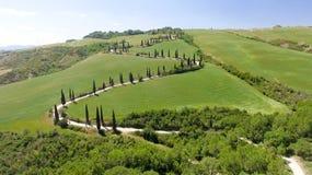 Vista aerea stupefacente della strada di bobina della campagna della Toscana in sprin Immagine Stock
