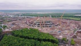 Vista aerea su area della costruzione di grande arena di sport moderna, gru di costruzione enormi stock footage