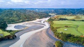Vista aerea su un ponte che attraversa un fiume che passa la valle della montagna Regione di Taranaki, Nuova Zelanda Fotografia Stock