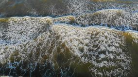 Vista aerea sulla cima Volo basso sopra le onde che vengono a puntellare L'onda sotto la tonalità forma un gran numero di schiuma archivi video