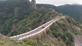 Vista aerea - un'automobile sola guida con un livello stretto e pericoloso della strada nelle montagne verdi Serpentina al livell stock footage