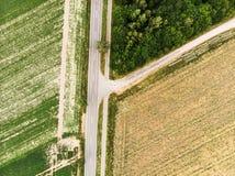 Vista aerea verticale astratta del ramo di un percorso da una strada campestre, con i campi, i campi ed il terreno boscoso Immagine Stock Libera da Diritti