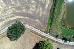 Vista aerea verticale sopra un percorso accanto ad un campo raccolto e un prato con una piccola stalla vicino ad un fossato stret fotografia stock libera da diritti