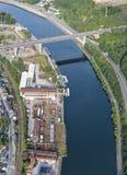 Vista aerea: viadotto sopra un fiume vicino ad un cantiere navale Fotografia Stock