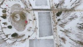 Vista Aero do parque do inverno da cidade Pista de patinagem no lago congelado Divertimento da família do inverno filme
