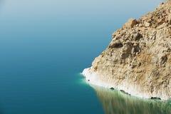 Vista al acantilado en la orilla de mar muerta con la reflexión en el agua en Jordania Foto de archivo