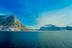 Vista al aire libre de escenas costeras de parcial enorme de las montañas cubierto con el durig de la nieve un viaje en Hurtigrut Foto de archivo