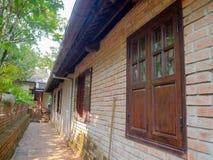 Vista al aire libre de un pasillo de una casa, de ventanas, de puertas y de un strucure rústico y clásico del edificio, con una p Foto de archivo libre de regalías