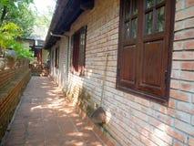 Vista al aire libre de un pasillo de una casa, de ventanas, de puertas y de un strucure rústico y clásico del edificio, con una p Fotografía de archivo