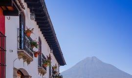 Vista al aire libre del balcón con algunas flores en un pote de edificio antiguo en la calle principal de la ciudad de Antigua co foto de archivo libre de regalías