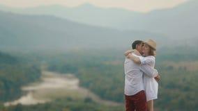 Vista al aire libre romántica de los pares cariñosos felices La mujer rubia hermosa es que besa y de abrazo de su novio en almacen de metraje de vídeo