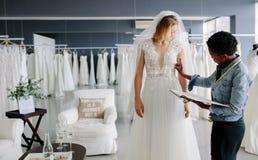 Vista al diseñador que cabe el vestido nupcial a la mujer en boutique fotografía de archivo