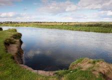 Vista al fiume con le riflessioni ed il cielo nuvoloso blu Fotografie Stock Libere da Diritti