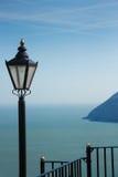 Vista al mar con la linterna y las verjas de la calle Foto de archivo libre de regalías
