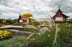 Vista al parco con i fiori variopinti e hous tailandese tradizionale Immagini Stock