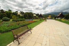 Vista al percorso con pochi banchi attraverso il giardino che caratterizza t Fotografie Stock