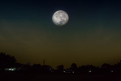 Vista al pueblo para ver la Luna Llena subir Imagen de archivo libre de regalías