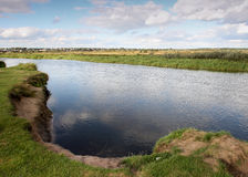 Vista al río con reflexiones y el cielo nublado azul Fotos de archivo libres de regalías