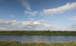 Vista al río con reflexiones y el cielo nublado azul Foto de archivo libre de regalías