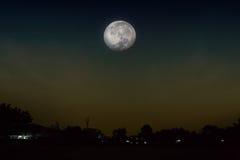 Vista al villaggio per vedere la luna piena aumentare Immagine Stock Libera da Diritti