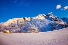 Vista all'aperto della casa di legno bianca coperta di neve e di mountaing enorme dietro nell'inverno nevoso nel Circolo polare a fotografia stock libera da diritti