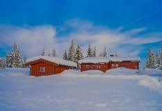 Vista all'aperto di neve in pini durante un inverno pesante e le case rosse di legno tipiche Fotografia Stock