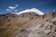 Vista alla cima innevata della montagna con cielo blu su fondo Immagini Stock