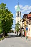 Vista alla via con gli alberi, le case e la chiesa cristiana verdi di tutti i san Immagine Stock Libera da Diritti