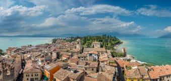 Vista alle costruzioni nel villaggio di Sirmione dalla polizia del lago in Italia fotografia stock libera da diritti