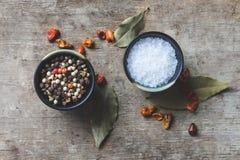 Vista alta e superiore di fine dei peperoni, foglie della baia e sale grosso e quattro spezie freddi in contenitori ceramici sull fotografia stock