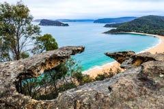 Vista alta sobre o oceano e a praia através do afloramento rochoso imagens de stock