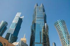 Vista alta vicina dei grattacieli moderni con la facciata di vetro finanziaria ed il centro di affari in Doha, Qatar immagini stock