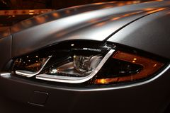 Vista alta vicina del faro di lusso grigio d'argento dell'automobile sportiva immagine stock