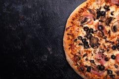 Vista alta vicina della cima di pizza al forno fresca su fondo di legno scuro Immagine Stock
