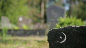 Vista alta vicina di mezza luna, simbolo crescente della luna su un monumento della tomba del granito in un cimitero un giorno so stock footage