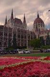 Vista amplia del edificio del parlamento en Budapest, Hungría y jardín con las flores Imagenes de archivo