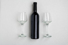 Vista angular aérea de uma grande garrafa do vinho tinto, vidros bebendo no fundo branco Fotos de Stock