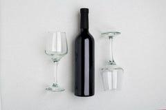 Vista angulosa de arriba de una botella grande del vino rojo, vidrios de consumición en el fondo blanco Imagen de archivo libre de regalías