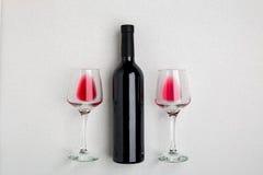Vista angulosa de arriba de una botella grande del vino rojo, vidrios de consumición en el fondo blanco Fotos de archivo