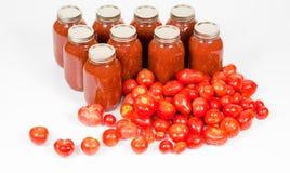 Vista angulosa superior de tomates con los tarros de la salsa de tomate Imagenes de archivo