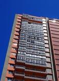 Vista angulosa vertical de un bloque de apartamentos concreto alto con los balcones contra un cielo azul imágenes de archivo libres de regalías