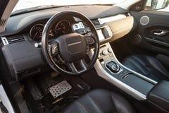 Vista ao interior da terra Rover Evoque com painel, pulso de disparo, sistema de meios, assentos e shiftgear dianteiros ap?s a li fotografia de stock
