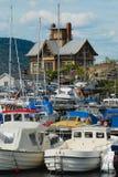 Vista ao porto com os barcos amarrados e a uma construção histórica no fundo em Drobak, Noruega imagem de stock
