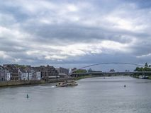 Vista ao Rio Mosa e à ponte Hoge Brug com um navio e umas construções velhas bonitas, em Maastricht, Países Baixos foto de stock royalty free