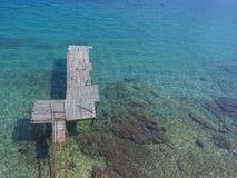 Vista areale sul pilastro di legno misero con acqua blu del Mar Ionio, spiaggia di Faliraki, bagni di Alecos, isola di Corfù, Gre fotografia stock