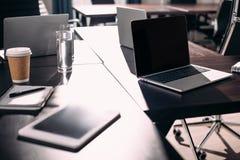vista ascendente cercana de la tableta digital, ordenadores portátiles, libro de texto, taza de papel del café en la tabla imagen de archivo