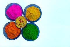 Vista ascendente cercana de los polvos orgánicos coloridos de Holi en cuencos azules del color foto de archivo