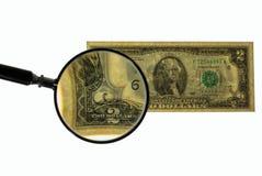 Vista ascendente cercana del billete de dólar más de dos de la lupa banknote foto de archivo libre de regalías