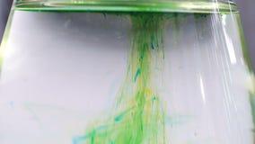 Vista ascendente cercana del cubilete del laboratorio con el colorante verde que disuelve almacen de metraje de vídeo